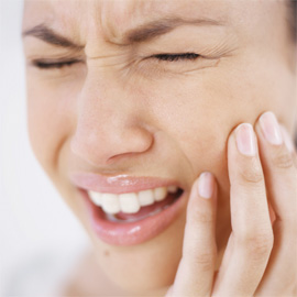 young woman holding her cheek in pain