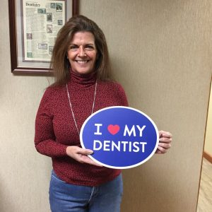 female patient holding up sign for dentist