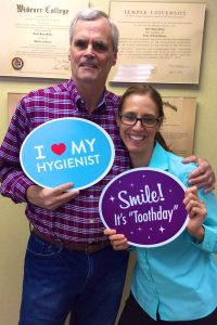 Male patient holding up sign with hygienist