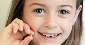 young girl smiling and holding up a lost tooth