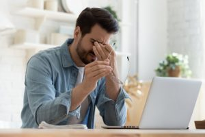 tired young man rubbing his eyes while sitting at desk with open laptop