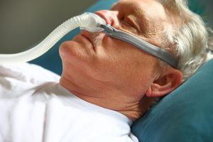Man wearing CPAP machine.