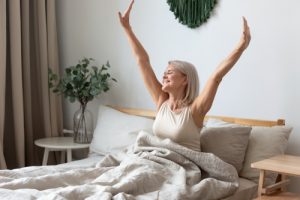 middle-aged woman waking up happy and well-rested