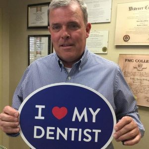 middle-aged male patient holding blue sign that says I love my dentist
